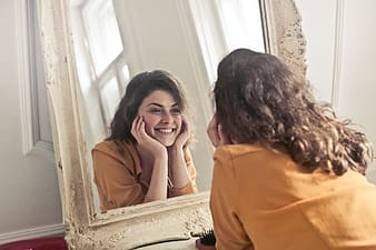 Young woman in Yellow Collared Shirt looking herself reflection in mirror at home