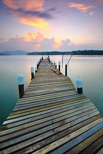 Photo of brown wooden dock and body of water