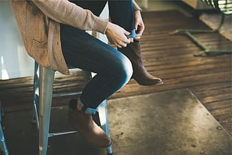 Woman in brown sweater and blue denim jeans sitting on brown wooden bench