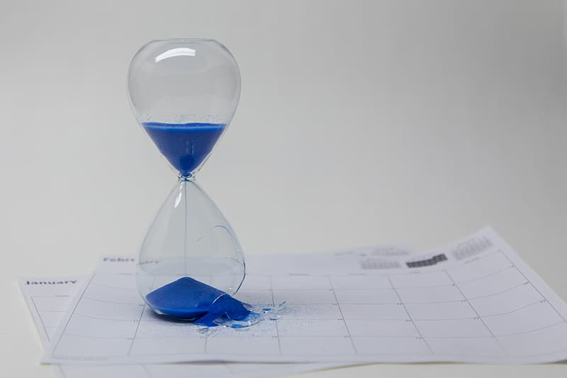 Clear glass hour glass on white paper