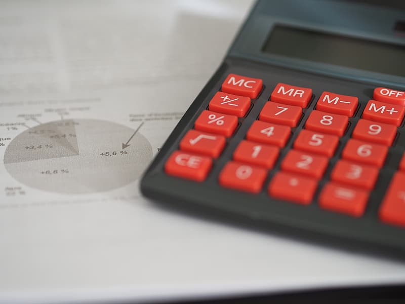 Black and red electronic calculator beside a pie chart