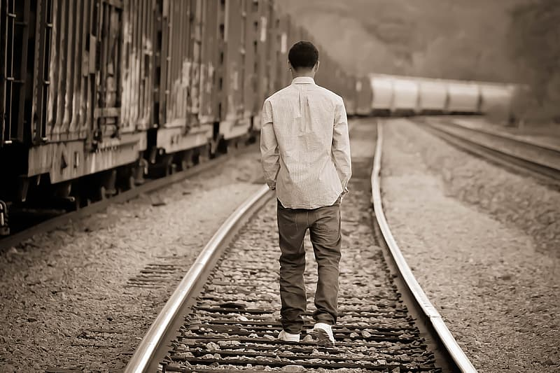 Grayscale photo of man walking on train railway