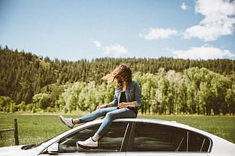 Woman in black long sleeve shirt and blue denim jeans sitting on car hood during daytime