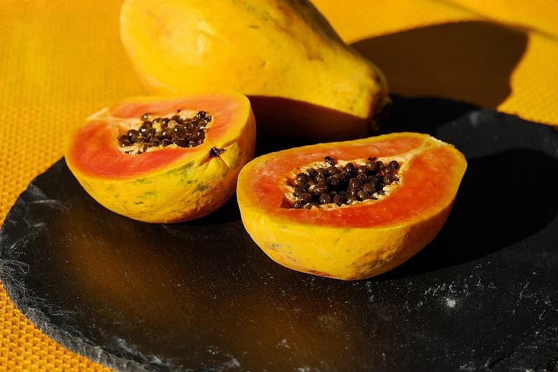 Sliced yellow fruit on black surface