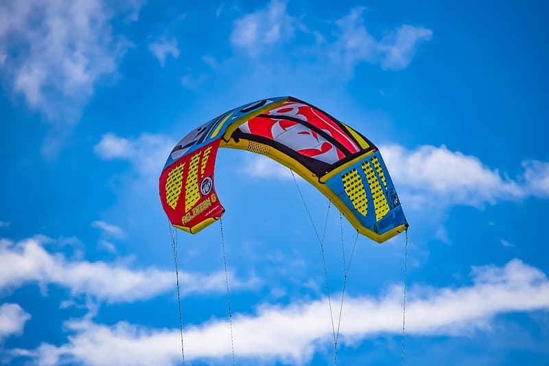 Red yellow and blue striped flag under blue sky during daytime