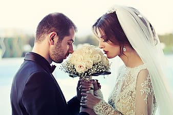 Photography of man and woman kissing white flowers
