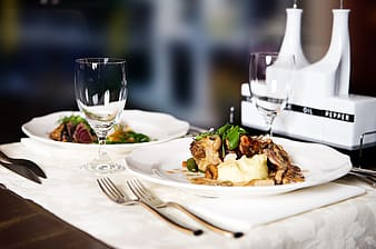 Cooked food on plates beside drinking glasses