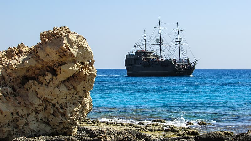 Black ship on sea near brown rock formation during daytime