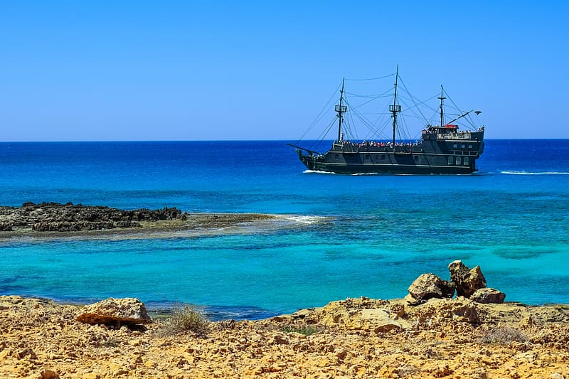 Brown ship on sea under blue sky during daytime