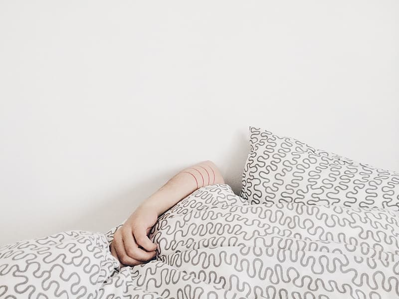 Person holding bed comforter beside wall