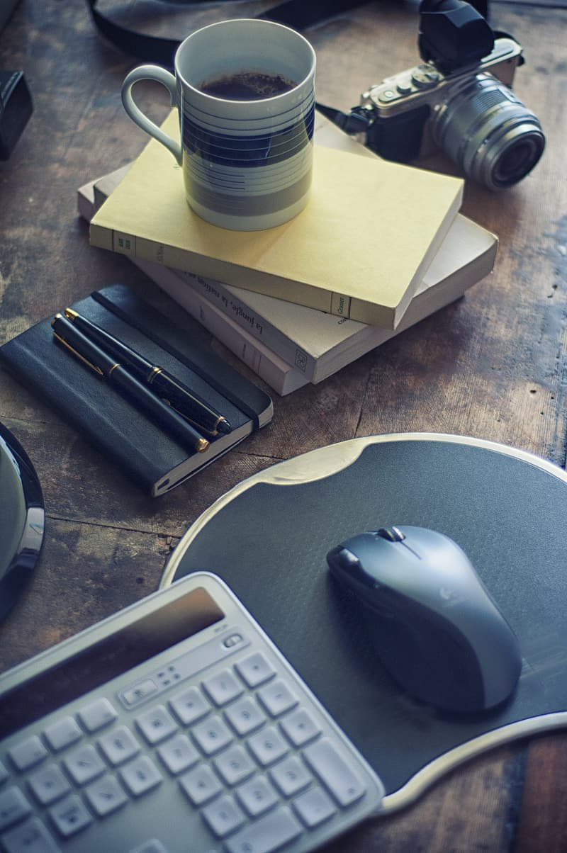 Computer keyboard, mouse with mouse pad, mug, books and camera on brown wooden board
