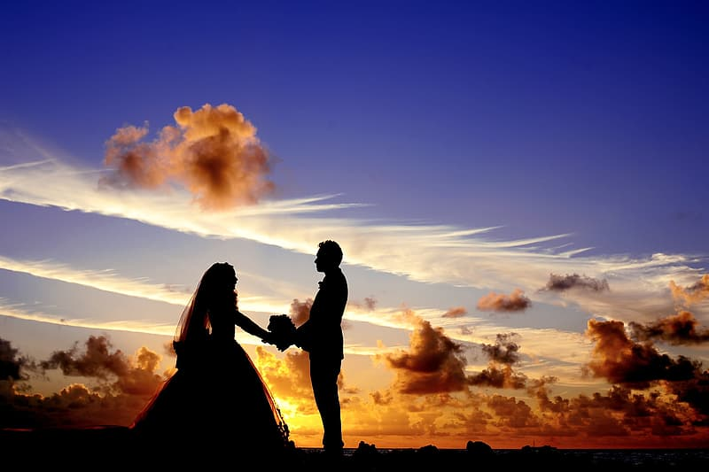 Silhouette of couple standing under the clouds