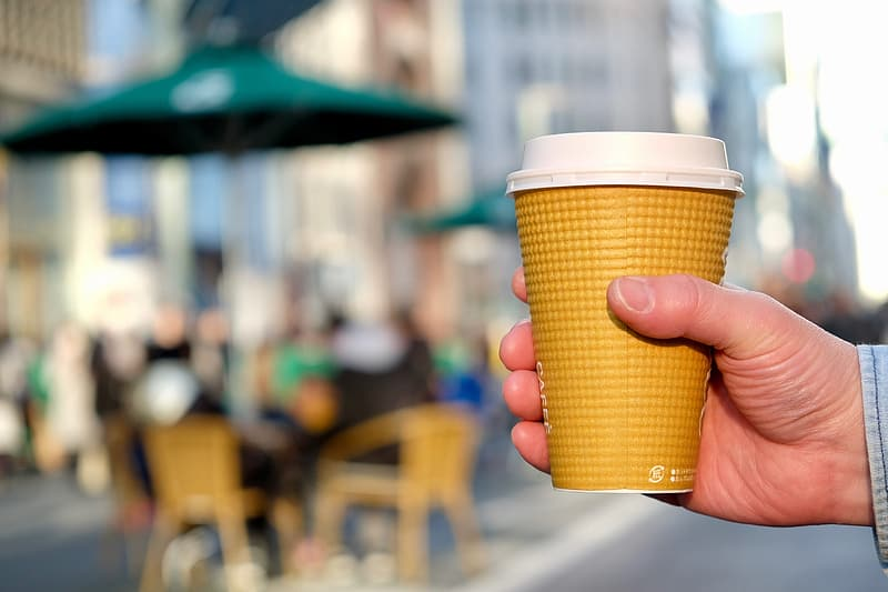 Person holding brown and white coffee cup