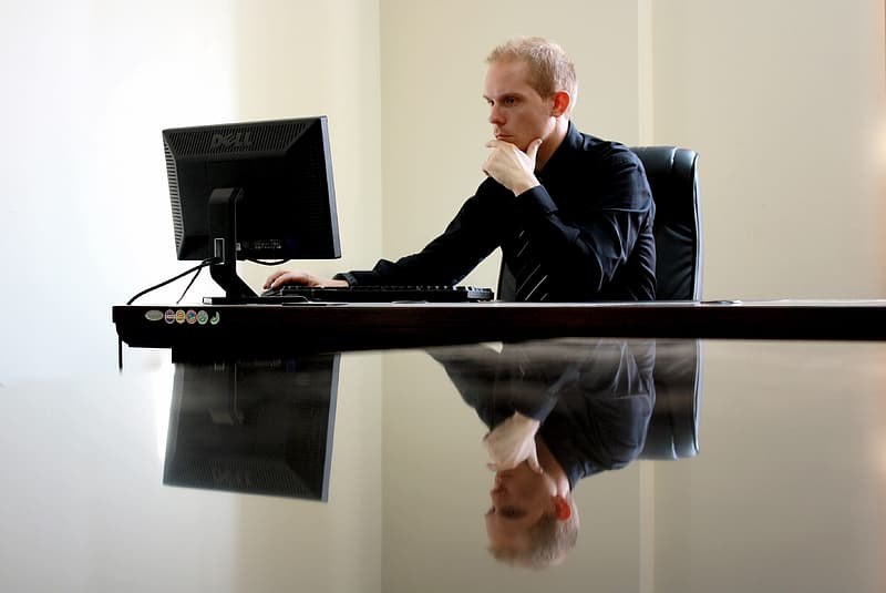 Man in black suit jacket sitting in front of black computer monitor