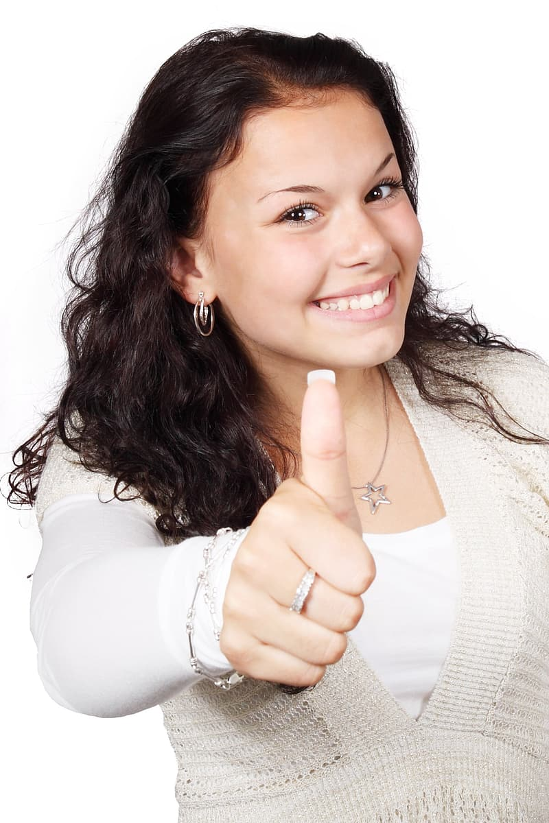 Woman in white shirt doing thumbs up hand gesture
