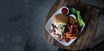 Burger with hand and ketsup on plate