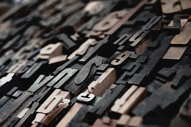 Shallow focus photography of embossed letters and special characters