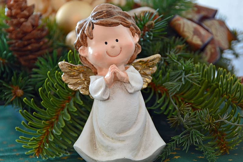 White and brown angel ornament on christmas tree