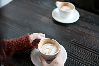 Person holding teacup with liquid