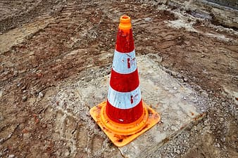 Orange and white traffic cone on brown sand