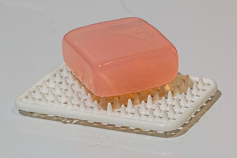 Photo of pink bar soap on white soap dish