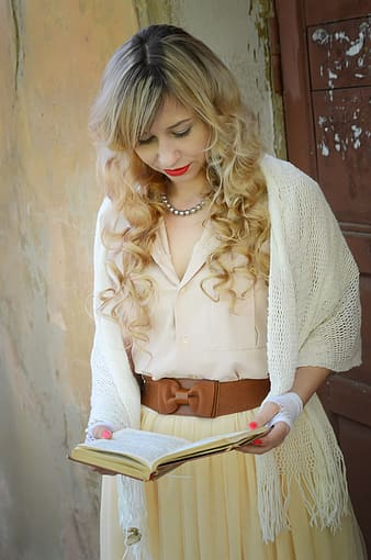 Woman wearing white knitted headscarf and beige bow-accent dress holding book