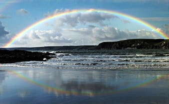 Photo of rainbow reflecting on calm body of water