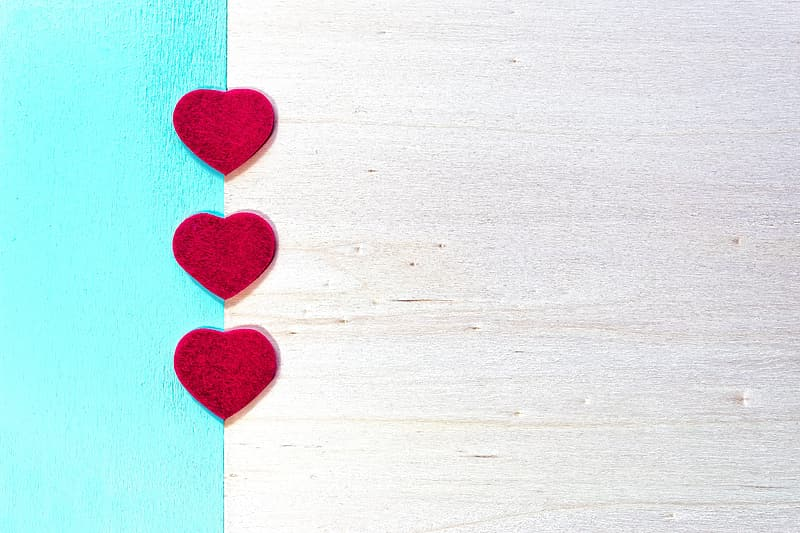 Red heart on white wooden surface