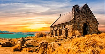 Landscape photography of brown and black brick church in the middle of brown grass near body of water during golden hour