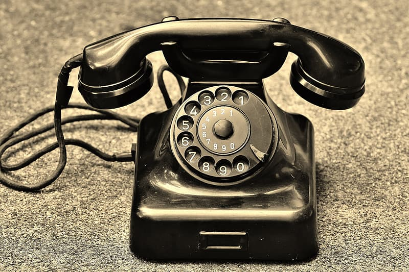 Black rotary telephone on brown and black marble surface