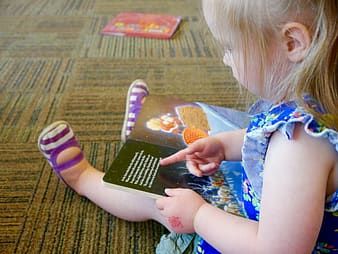 Girl rearing book while sitting on brown floor