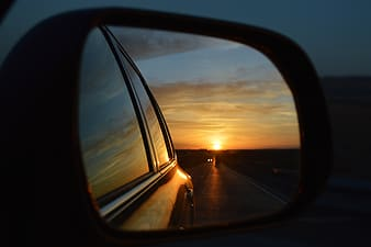 Vehicle side mirror showing following vehicle on road during sunset