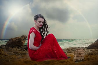Woman in red dress sitting on boulder near body of water