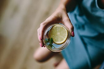 Person holding clear drinking glass with lemon juice