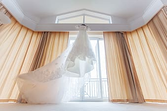 White wedding gown near window curtain