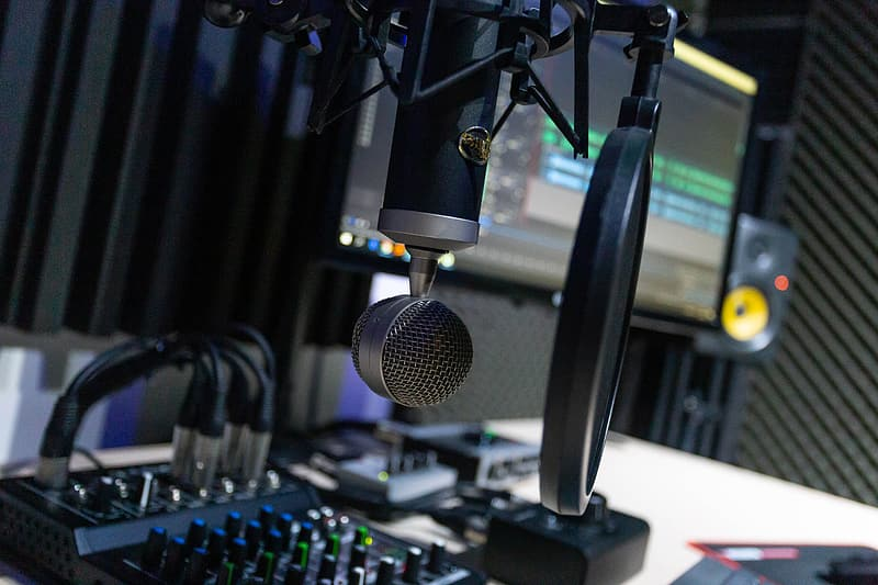 Black and gray microphone on black and green audio mixer