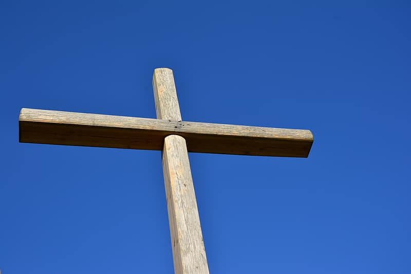 Close up photography of brown wooden cross under blue cloudy sky