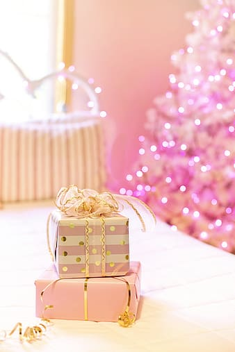 Gold gift box on pink and white polka dot textile