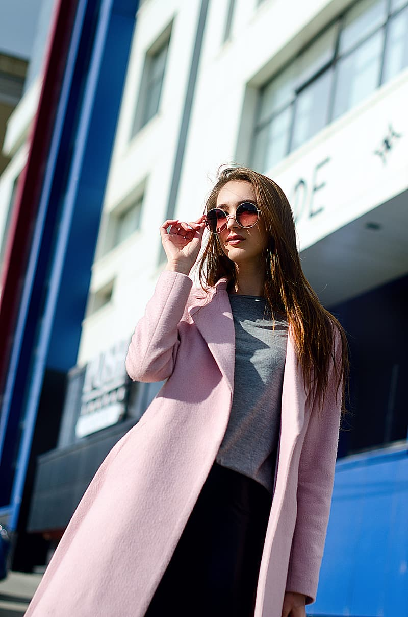 Woman in pink cardigan and black skirt wearing brown sunglasses