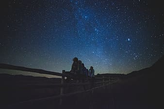 Silhouette of people sitting on wooden fence under starry night