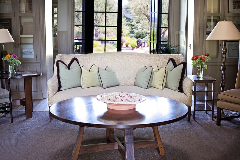 Beige floral sofa in front of round brown wooden coffee table