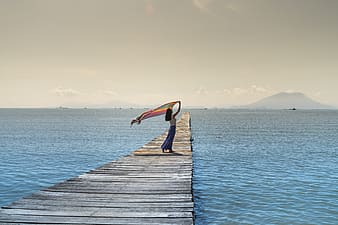 Woman holding textile standing on gray wooden sea dock during daytime