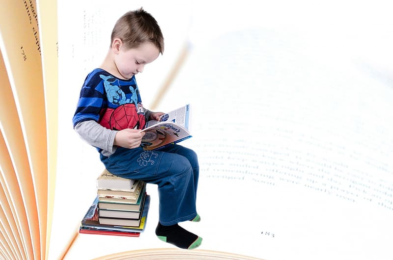Toddler in Spiderman printed shirt sitting down on pile of books reading book