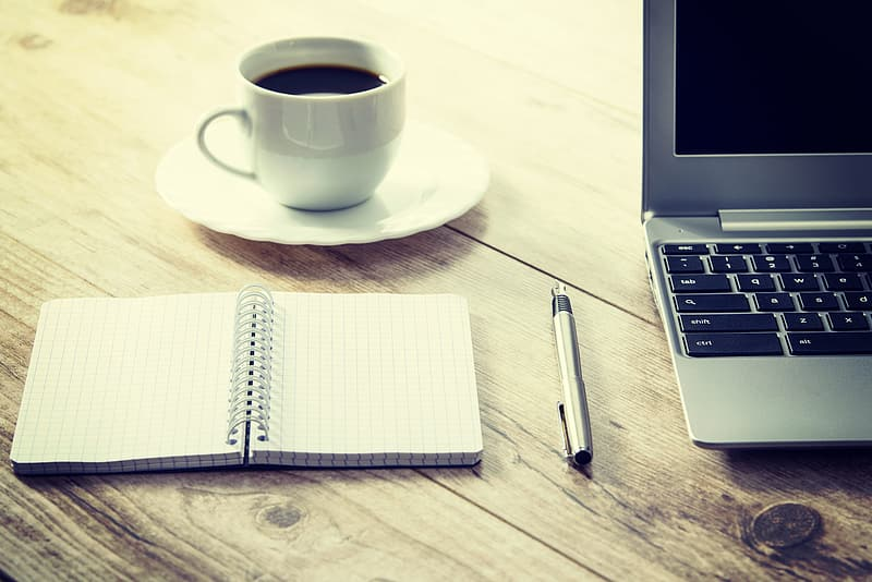 White cup and saucer beside gray laptop computer
