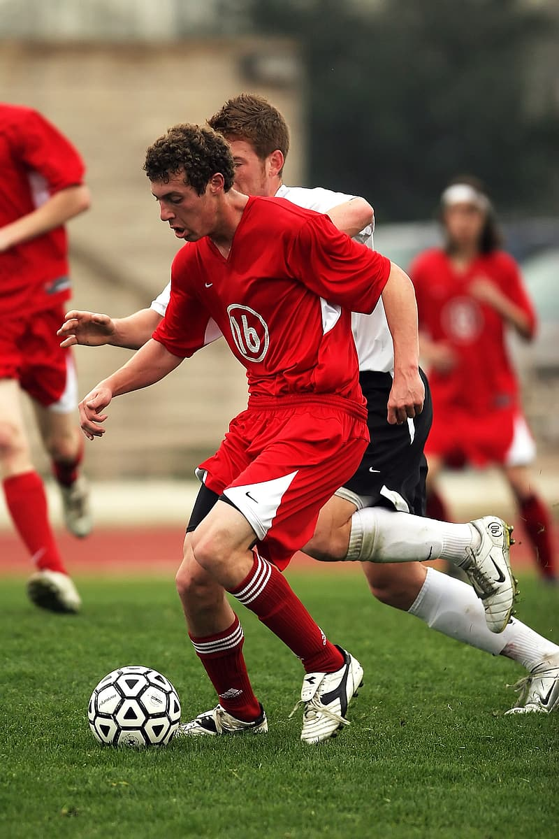 Man in red and white soccer jersey kicking soccer ball