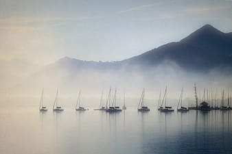 Brown boats on lake with fogs near mountain