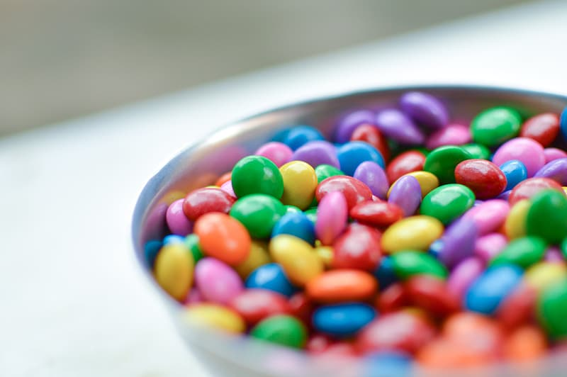 Assorted-color candy on grey bowl