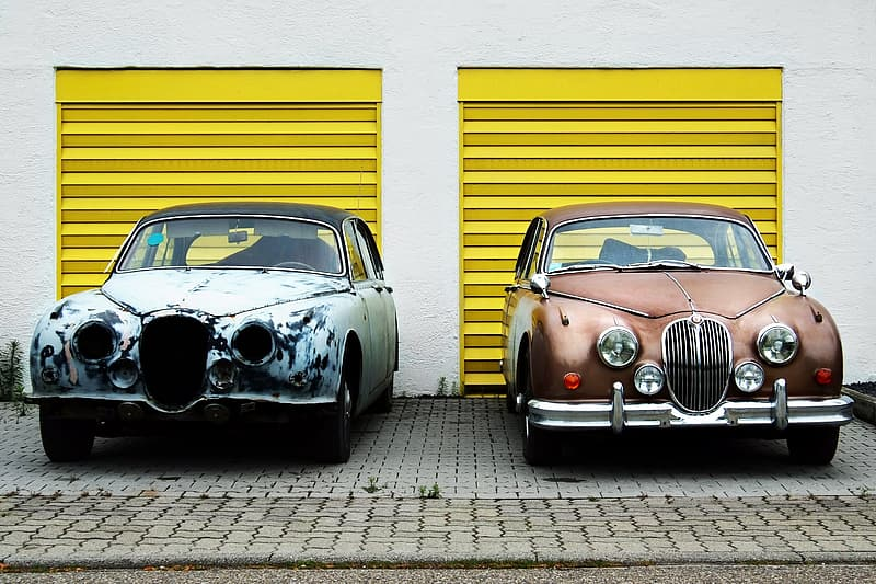 Black classic car parked beside yellow wall
