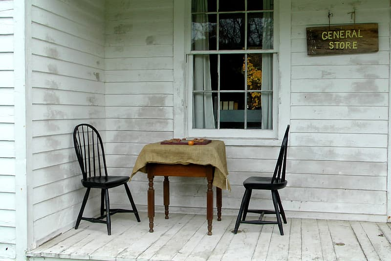 Two black windsor chairs in front of window