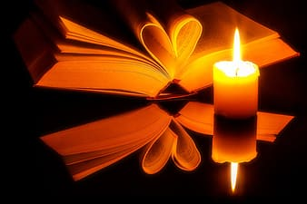 Yellow candle beside of book